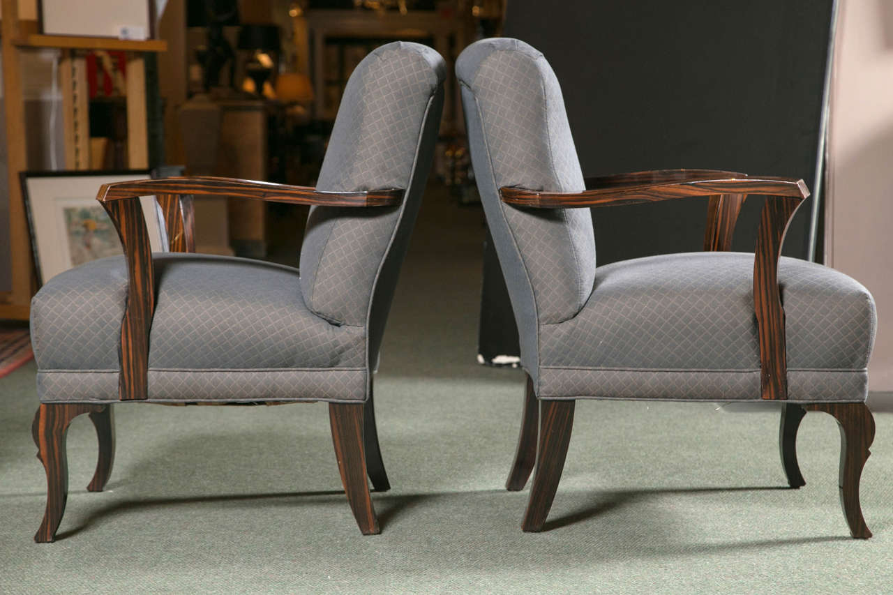 A pair of Art Deco upholstered seat & back armchairs with stylish accent arms and legs in Palisander wood.
