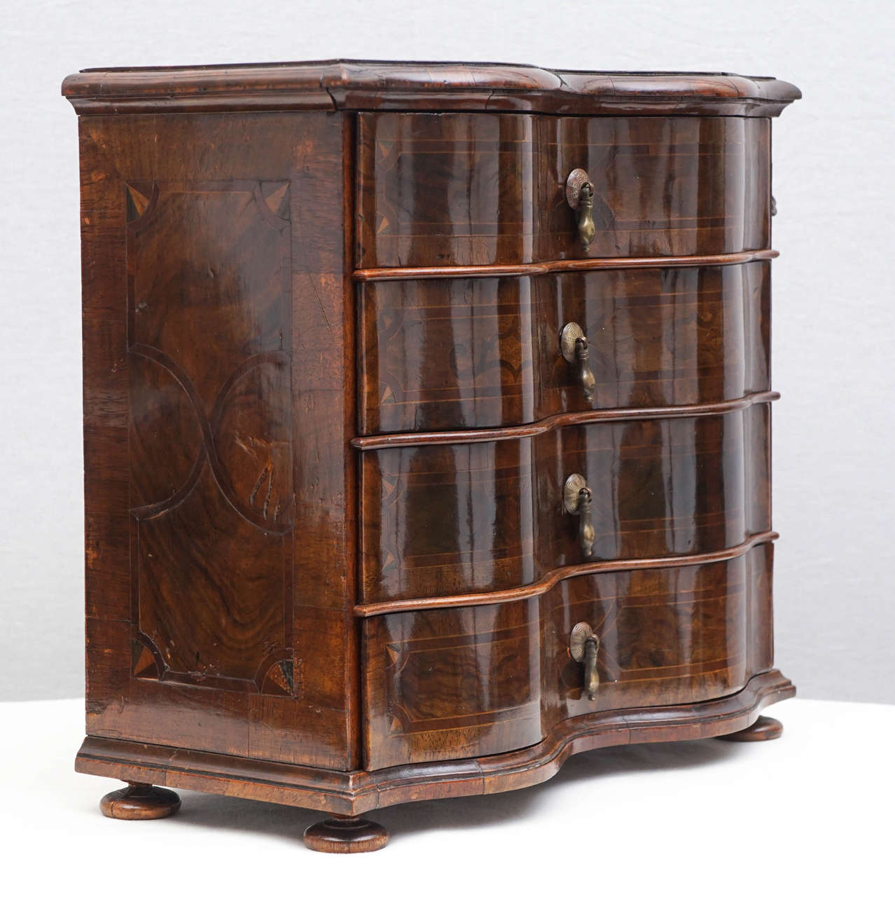 German Rococo-style walnut inlaid miniature serpentine-fronted chest of drawers, with locking device and key. Teardrop metal drawer pulls. Intricate locking device that secures all the drawers. Interior of all the drawers painted in precious metal