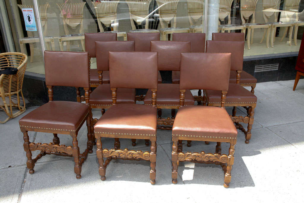 Set of ten dining chairs, Renaissance Revival style, in oak with brown leather upholstery, carved chair rails and brass studded leather.