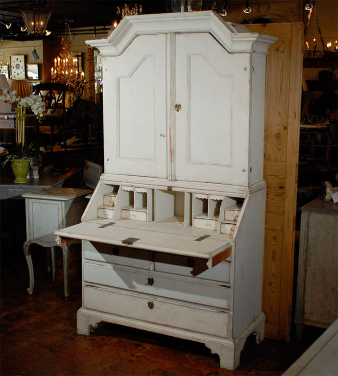A simple lovely Swedish secretary in two parts.  With a handsome crown molding pediment and the base with a fall front desk with multiple drawers.