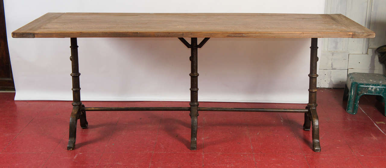 The stylish Versailles country iron metal table is composed of three bistro style legs braced at top and bottom supporting a rustic table top made from reclaimed teak wood with beautiful patina. The 1.25