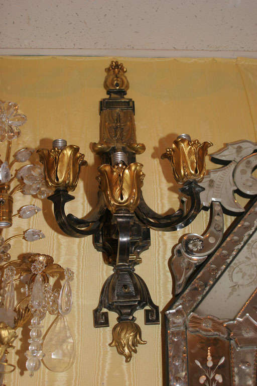Fabulous two-toned patinated and gilt bronze three-arm wall sconces in the Caldwell style. Stock number: L80.