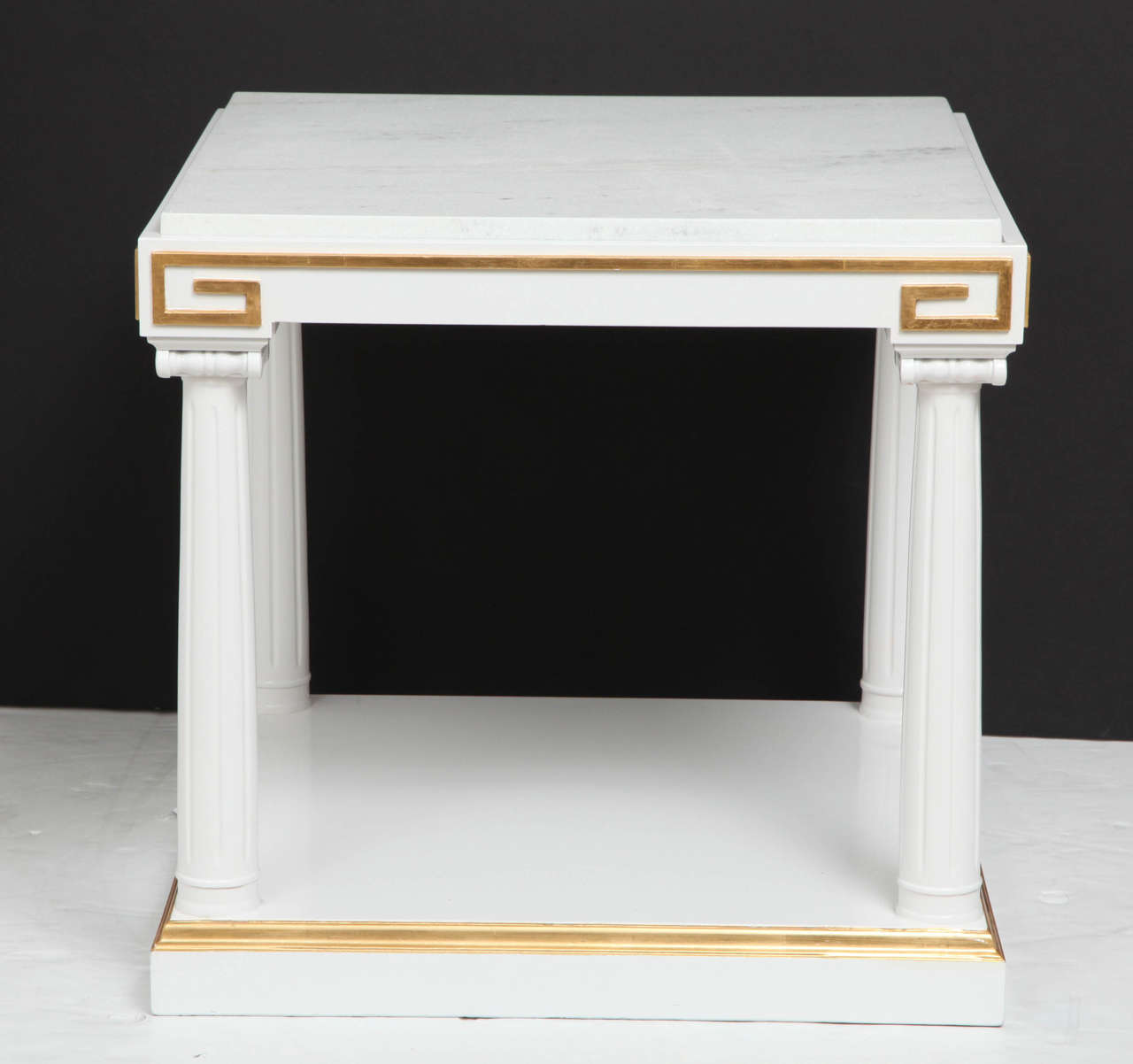 Fantastic pair of neoclassical side tables with fluted column supports and capitals in white lacquer. Tables also feature gold leaf Greek key details and white marble quartz inset tops.