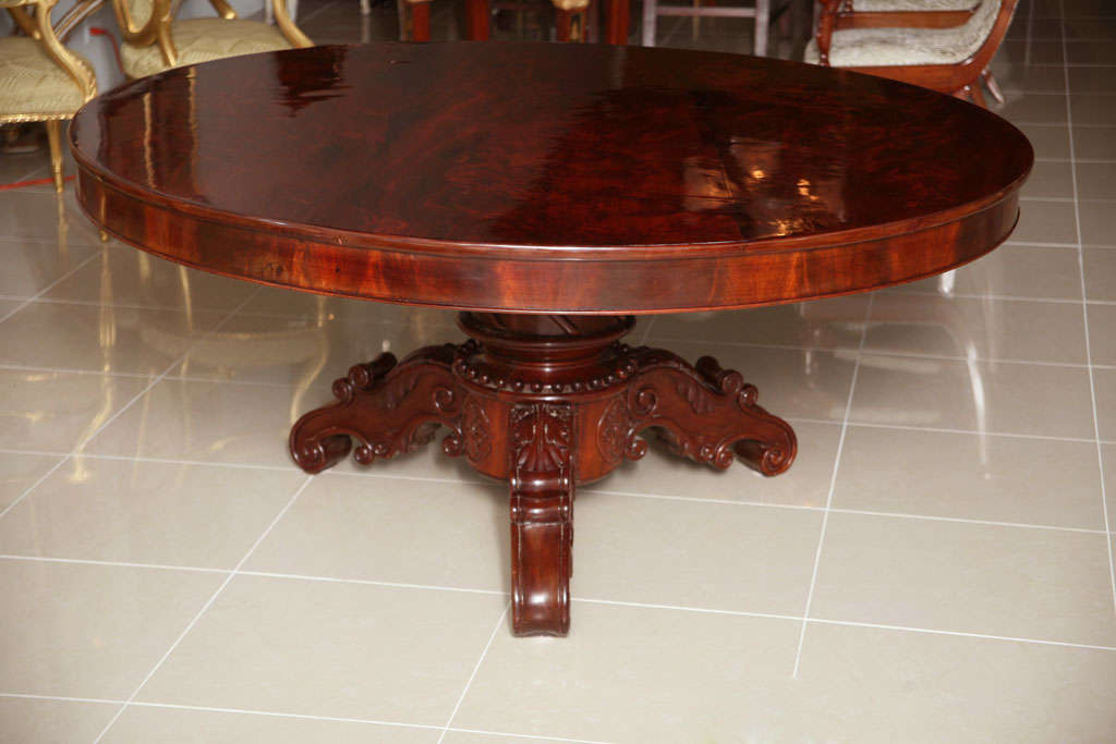 The flame mahogany top above a pedestal with elaborate carving, beading, rosettes, resting on three carved legs with similar motifs.