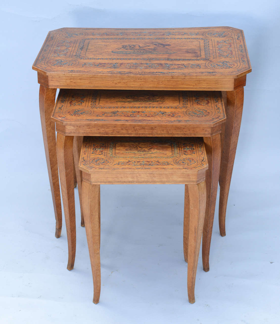Set of three nesting tables, of wood, each rectangular shaped with canted corners, etched with leafy, scrolling designs hightlighted with delicate handpainting, centered with horse drawn chariot and rider.  Stock ID: D6738