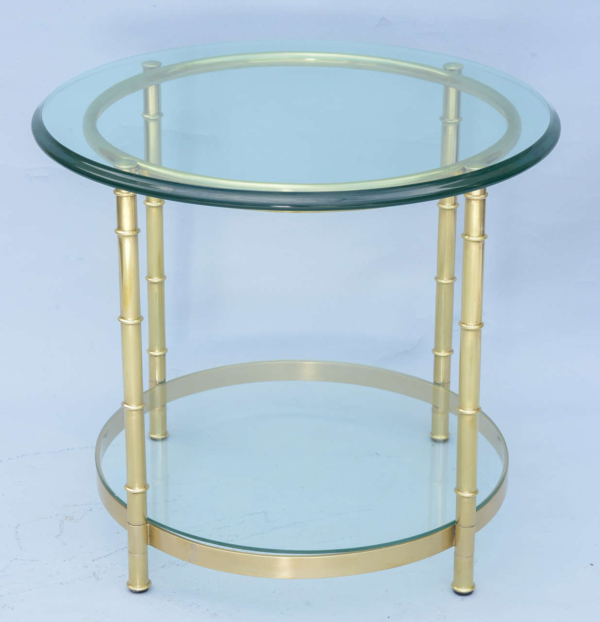 End or side table, of polished brass, its round glass top raised on faux bamboo legs, joined by ring apron and shelf-stretcher.  Stock ID: D7191