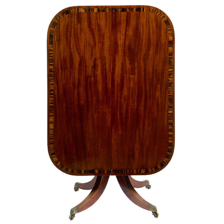 Regency mahogany breakfast table. Of rectangular form with rounded corners and crossbanded in Coromandel wood, raised on a ring-turned pedestal and four reeded down-swept legs with brass embossed caps and castors.