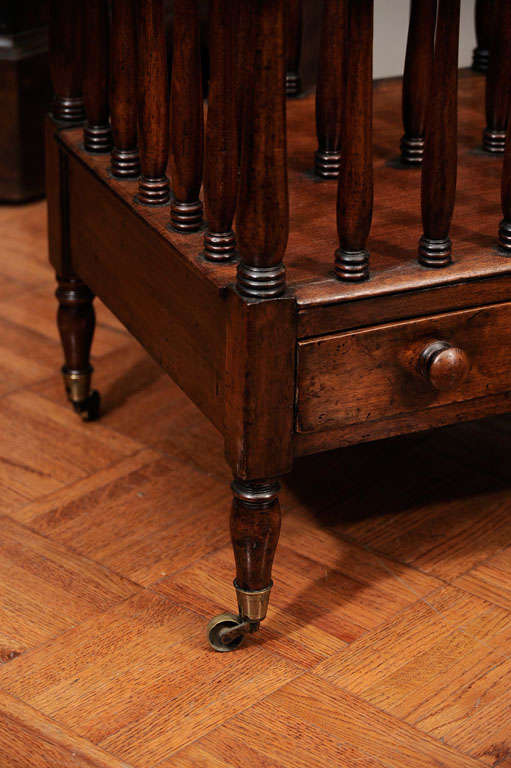 George III mahogany Canterbury with two rectangular divisions, turned splats above frieze drawer with ring turned tapering legs on brass feet and castors.