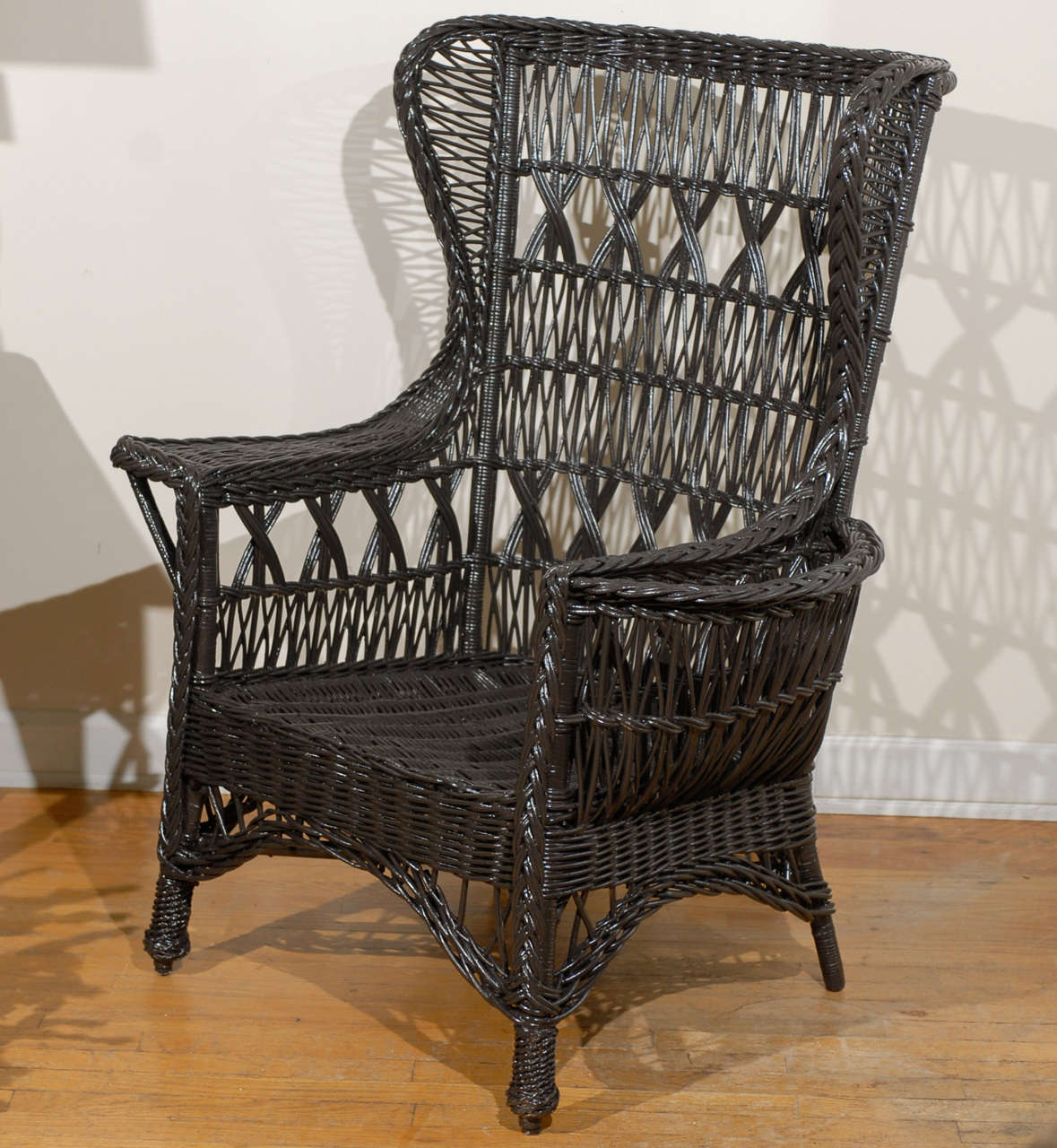 This is a beautiful brown antique American wicker wing chair in the Mission style with magazine pocket and woven pineapple feet in the front.  This chair is Bar Harbor style and very sturdy.  The chair was made in 1915-1920.  Please visit our