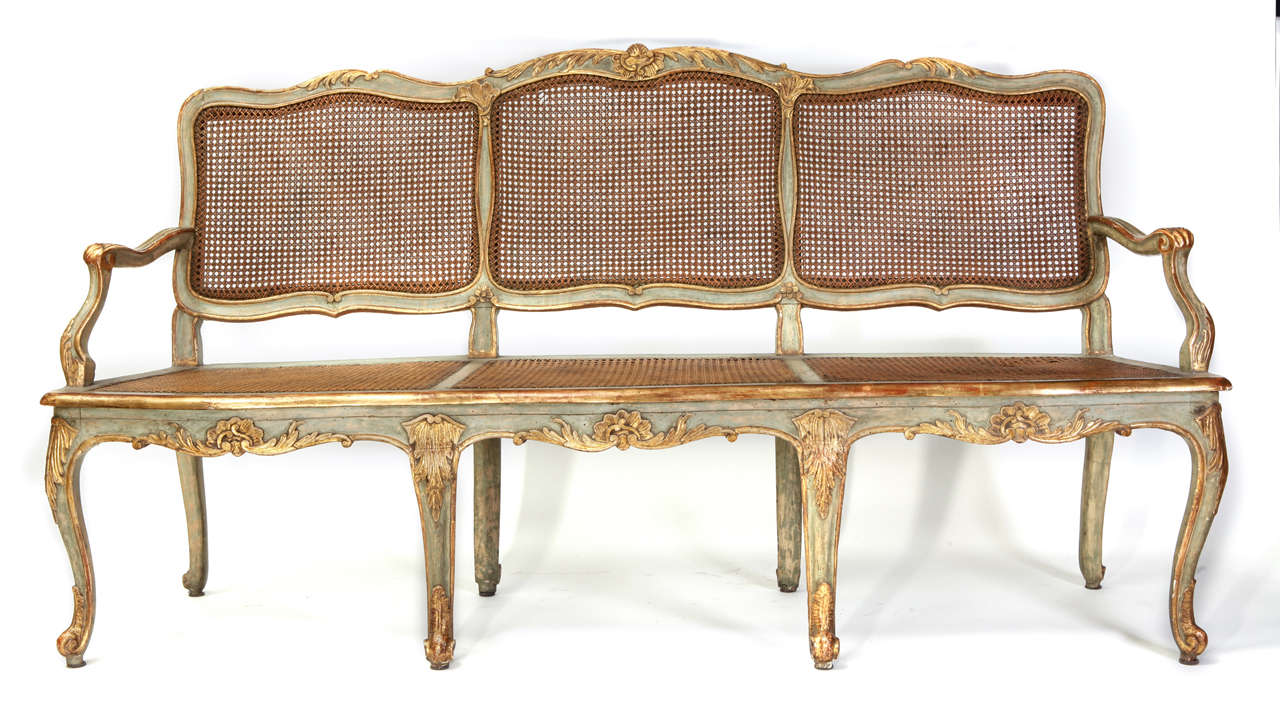 A fine Italian 18th century parcel-gilt and turquoise painted caned canape with a shaped back decorated with shell-carved crest, scrolling armrests on a serpentine seat on cabriole legs ending in scroll feet.