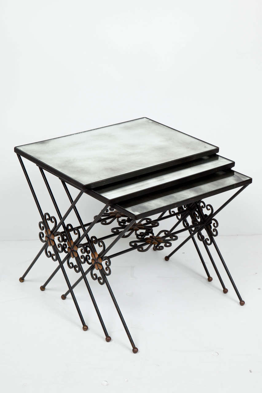 Set of three French Moderne wrought iron nesting tables with gilt accents and original silvered mercury glass mirror tops.