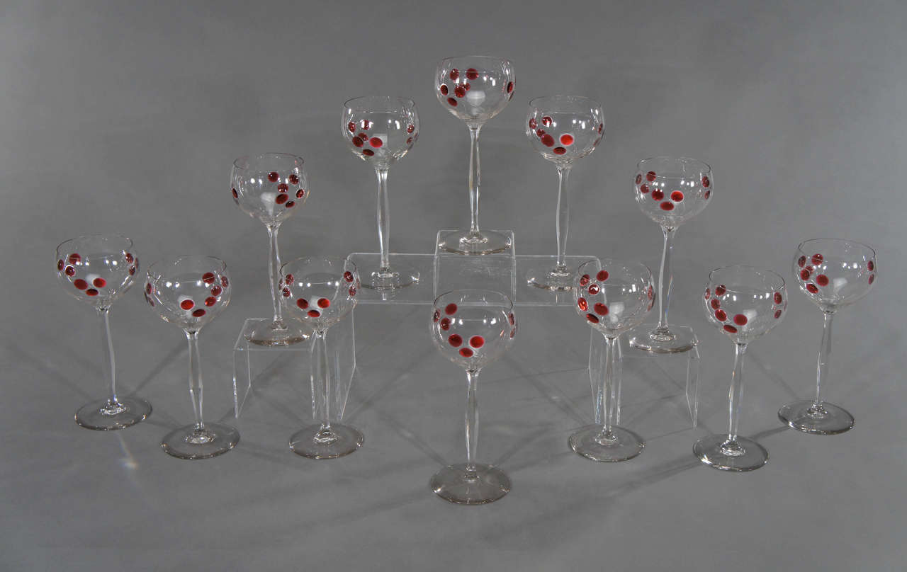 "A dramatic and rare set of 12 hand blown TALL crystal goblets with red marquetry ""balloons"" or ""cherries"" with engraved decoration. The elegant stems are panel cut, giving a wonderful feel to the glass.
