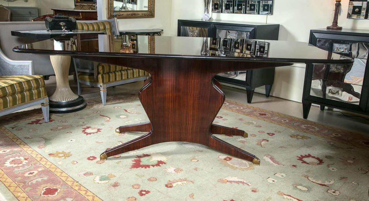A fine custom quality dining or conference table in the style of Osvaldo Borsani. The vase form pedestal base on brass casters of solid rosewood construction supporting the original wooden framed table surface, rarely seen, with the original paint