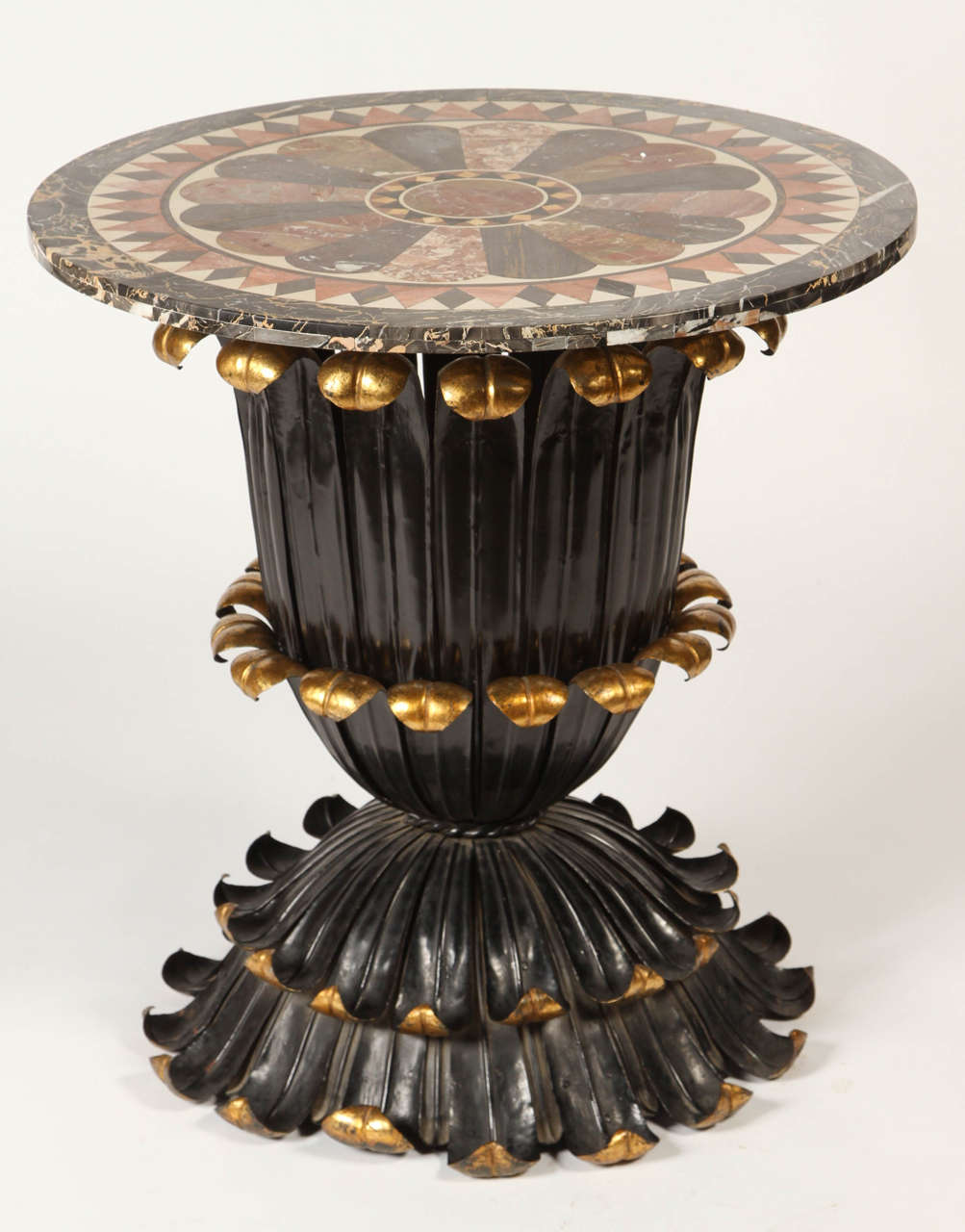 This stunning table from the late 19th century has a fantastic marble specimen top and a painted and gilt foliage-inspired base. The deep color palette contrasts wonderfully with the feminine organic silhouette. This table would be perfect for a