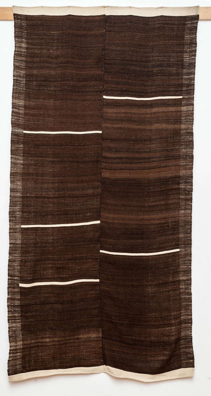 An unusual and highly graphic kilim, attributed to the Kurdish people located in the Mazandaran region in northern Persia, woven with natural dark brown wool with accents of ivory cotton for the asymmetrically placed horizontal stripes.  Flat-weaves
