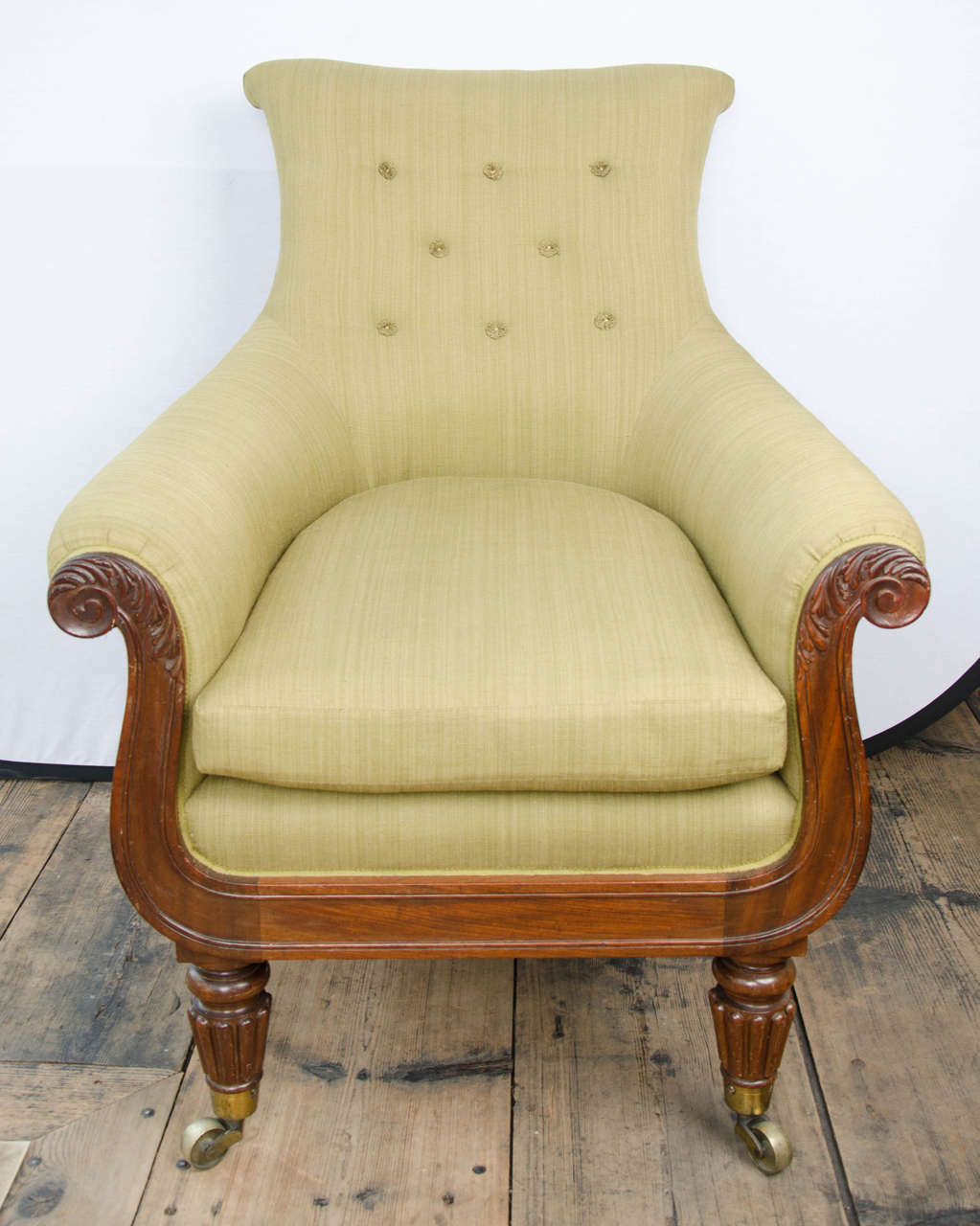 Regency mahogany library bergere in the manner of Gillows with outscrolled back and arms on reeded tapering legs.