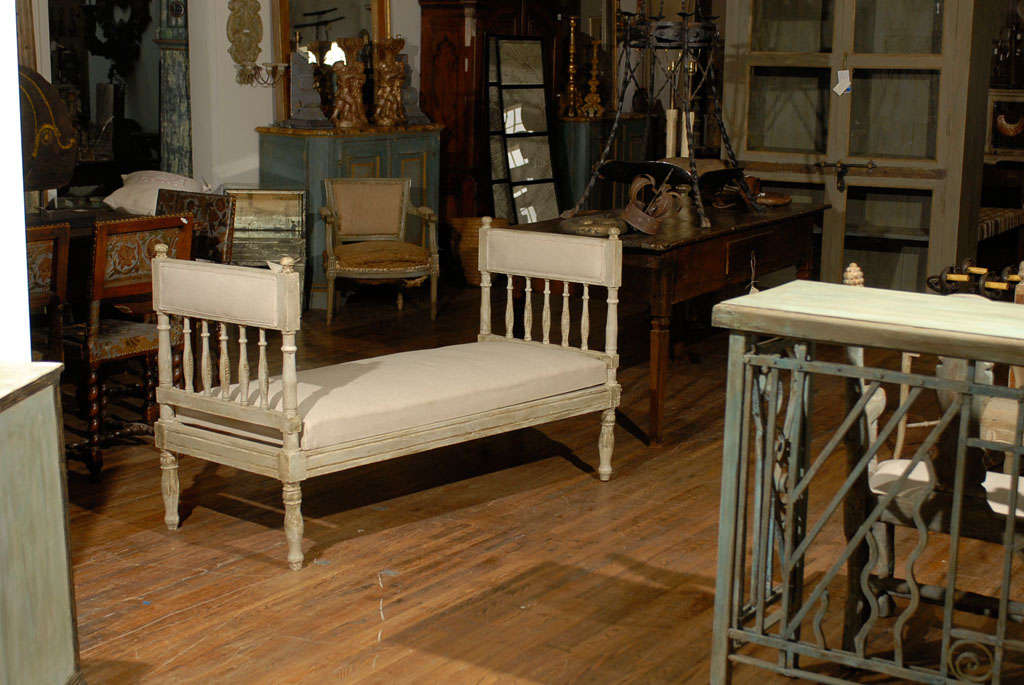 A mid-19th century Swedish Gustavian style painted wood daybed or bench with turned and carved spindles and upholstered top rail.  This Swedish Gustavian Style daybed has been reupholstered in Belgian linen.