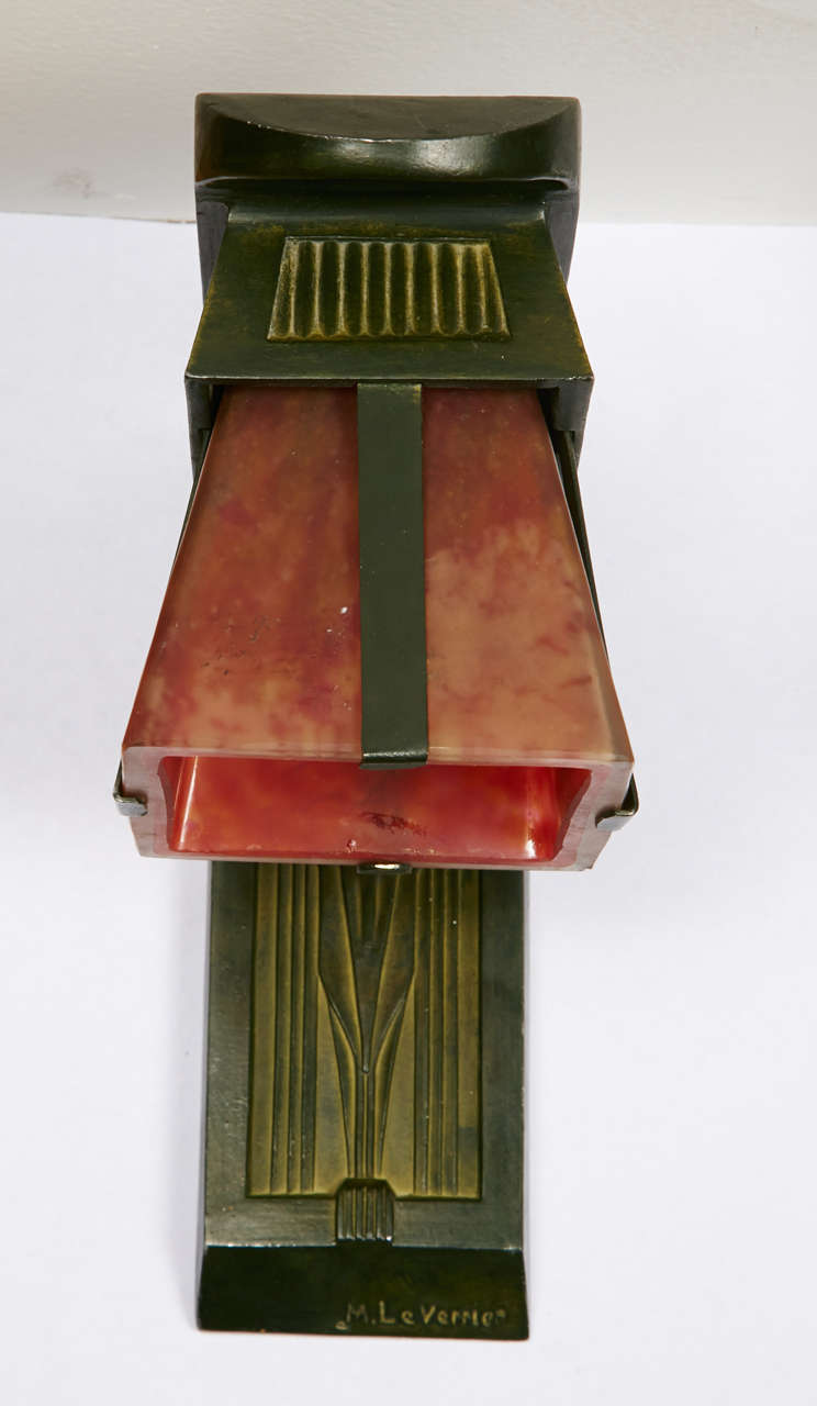Pair of sconces with a green patinated bronze structure. Pink orange colored glass shades. Signed 'M. Le Verrier'. French work, circa 1920-1930. Wired for European use.