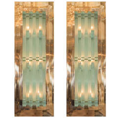 Pair of brass sconces with interweaving glass shade design