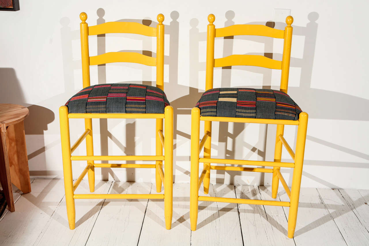 Bold yellow stools with newly reupholstered graphic African textile seats. Sold individually.