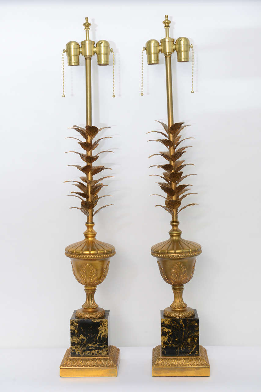 Featuring a double socket cluster, this pair of very elegant table lamps have a stem of gilt tole leaves rising from a column footed neoclassical urn with acanthus leaves over a black and gold faux marble painted metal base with a gilt acanthus leaf