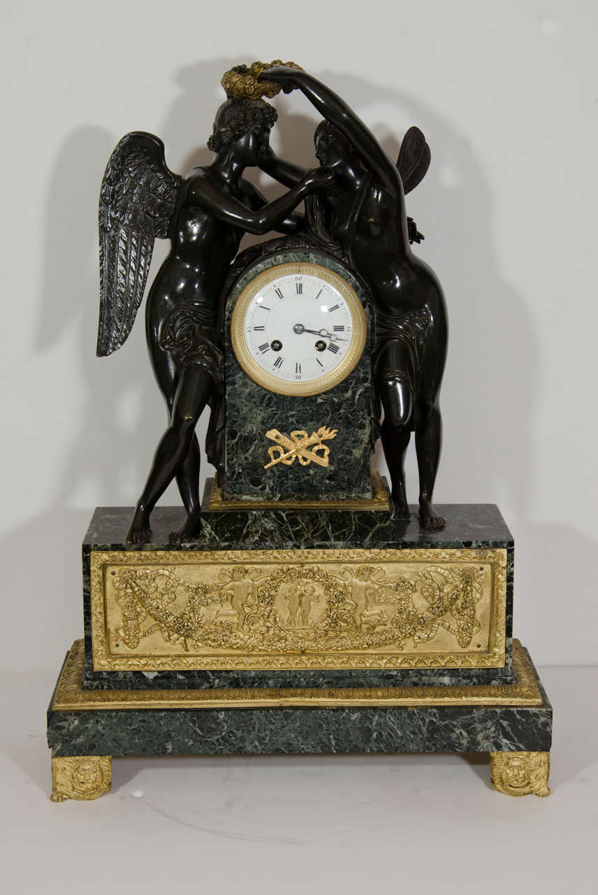 A Large Antique French Empire style figural patinated bronze, gilt bronze and green marble clock depicting two neoclassical figures.