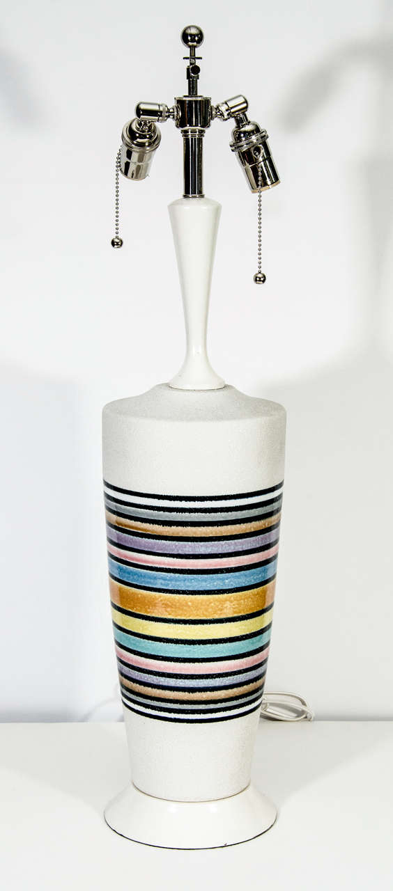 White ceramic stoneware with glazed pastel rings and white painted wood stem and base.