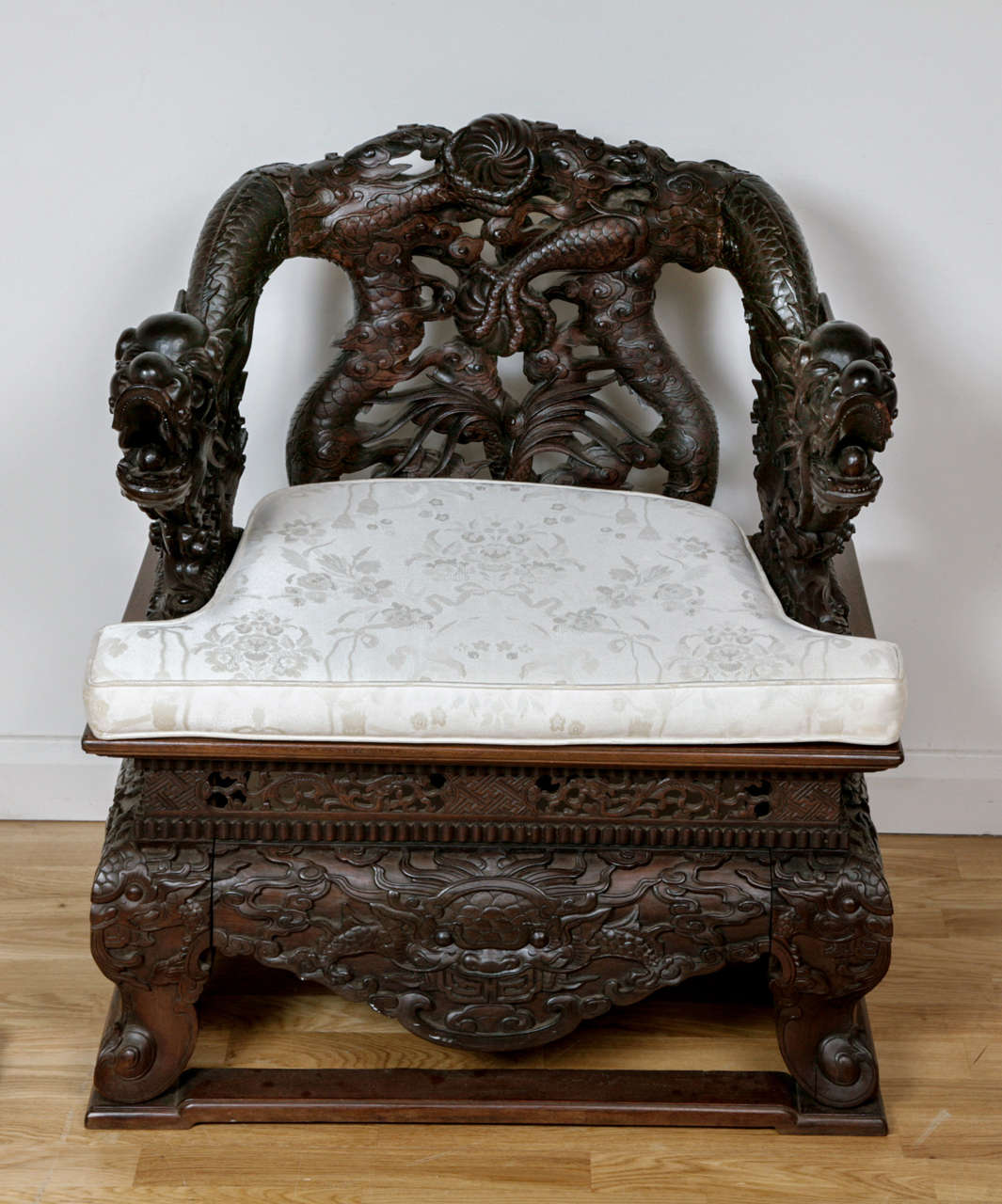 Profusely carved overall, the back and arms depicting two opposing dragons with entwined tails over a panelled seat with cream squab cushion, the low relief carved frame depicting swirling clouds and dragons.