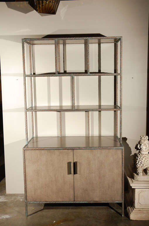 Modern Paul Marra bookcase shown in metal frame wrapped with embossed faux bronze, inset shelves and doors shown in gray wash. One in stock as shown. Can be custom-ordered.