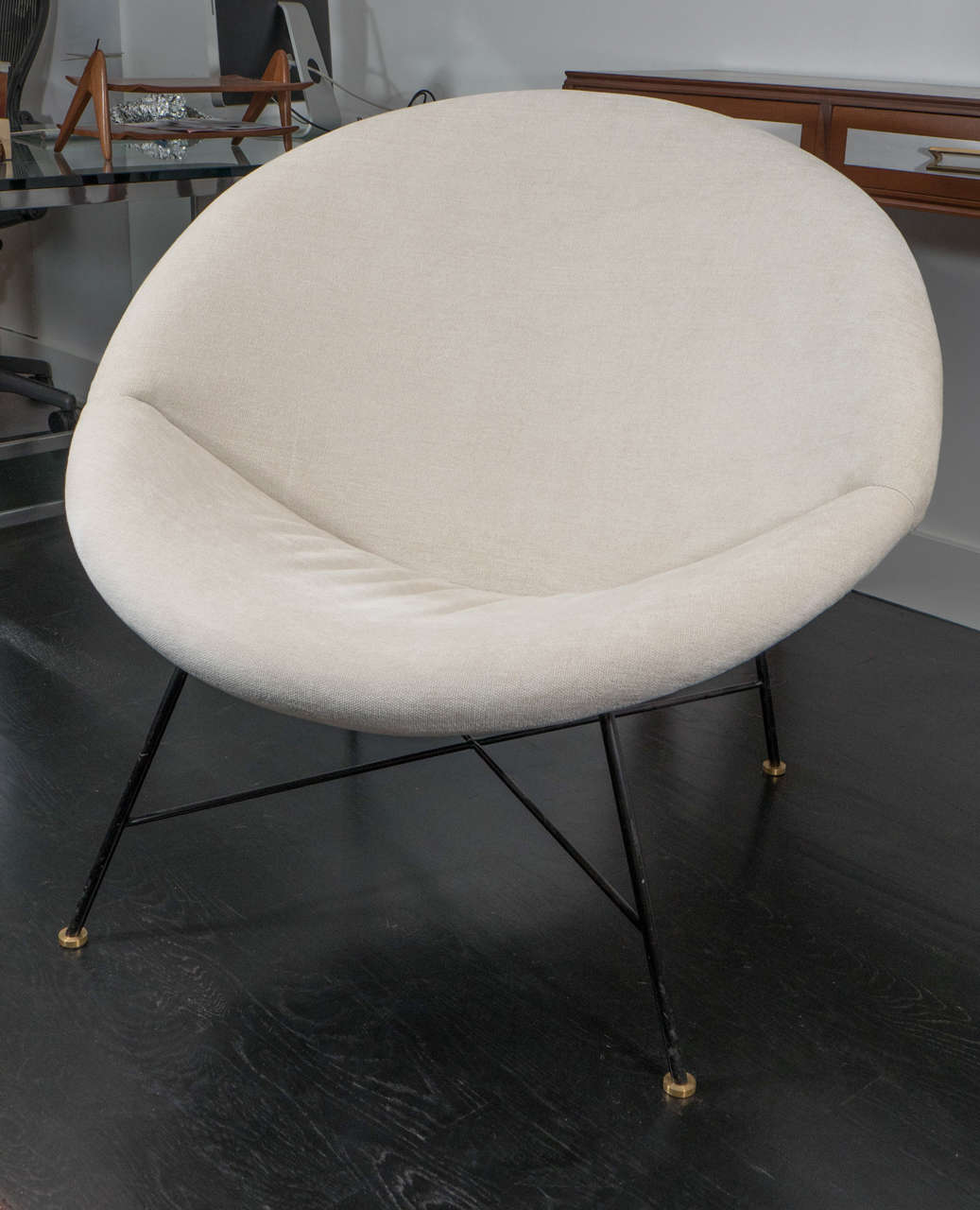 Pair of 1970s chairs designed in the style of Pierre Paulin. Round seat with middle seam on iron legs with brass feet.