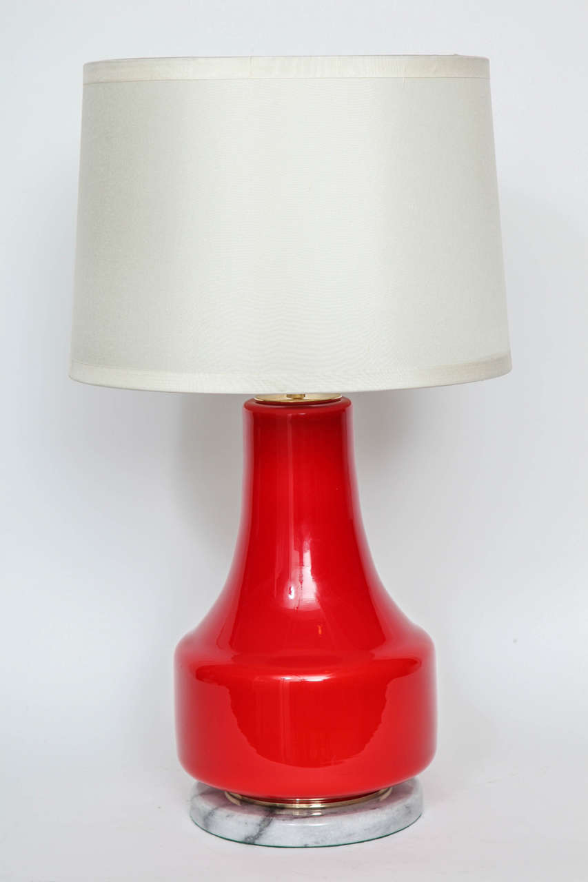 Italian Mid Century  poppy red glass lamps on a light grey marble base with brass detail and sockets. Each lamp has 1 socket, 100W max.
