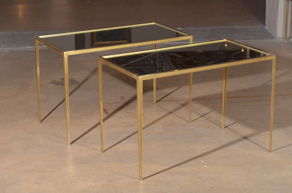 Pair of delicate crafted brass frame side tables with inset mirrored tops. Brass frame has matte detailing with traces of slight use.