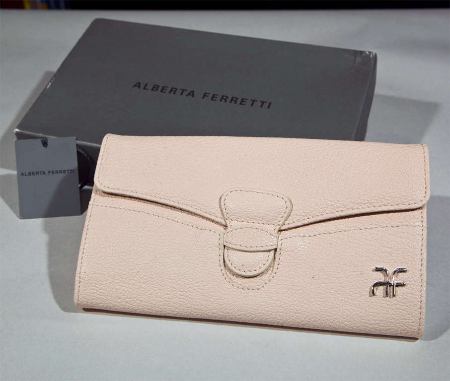 funkyfinders is pleased to present this beautiful pebbled leather, pretty-in-pale-pink clutch wallet from the house of alberta ferretti. a refined silver tone logo adorns the front in rather discreet fashion. 12 compartments are ready to house your