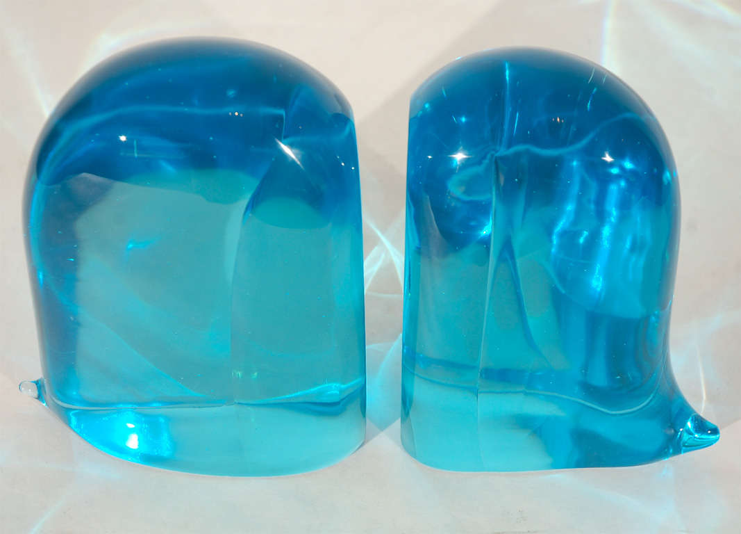 A striking pair of blue glass bookends with little tails. Dimensions given below are for the larger bookend. The smaller bookend measures 8.25