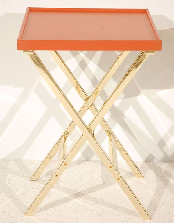 A chic pair of polished brass X-base side tables with rimmed leather-wrapped Hermes orange table tops. Tables are available individually for $3500 each.