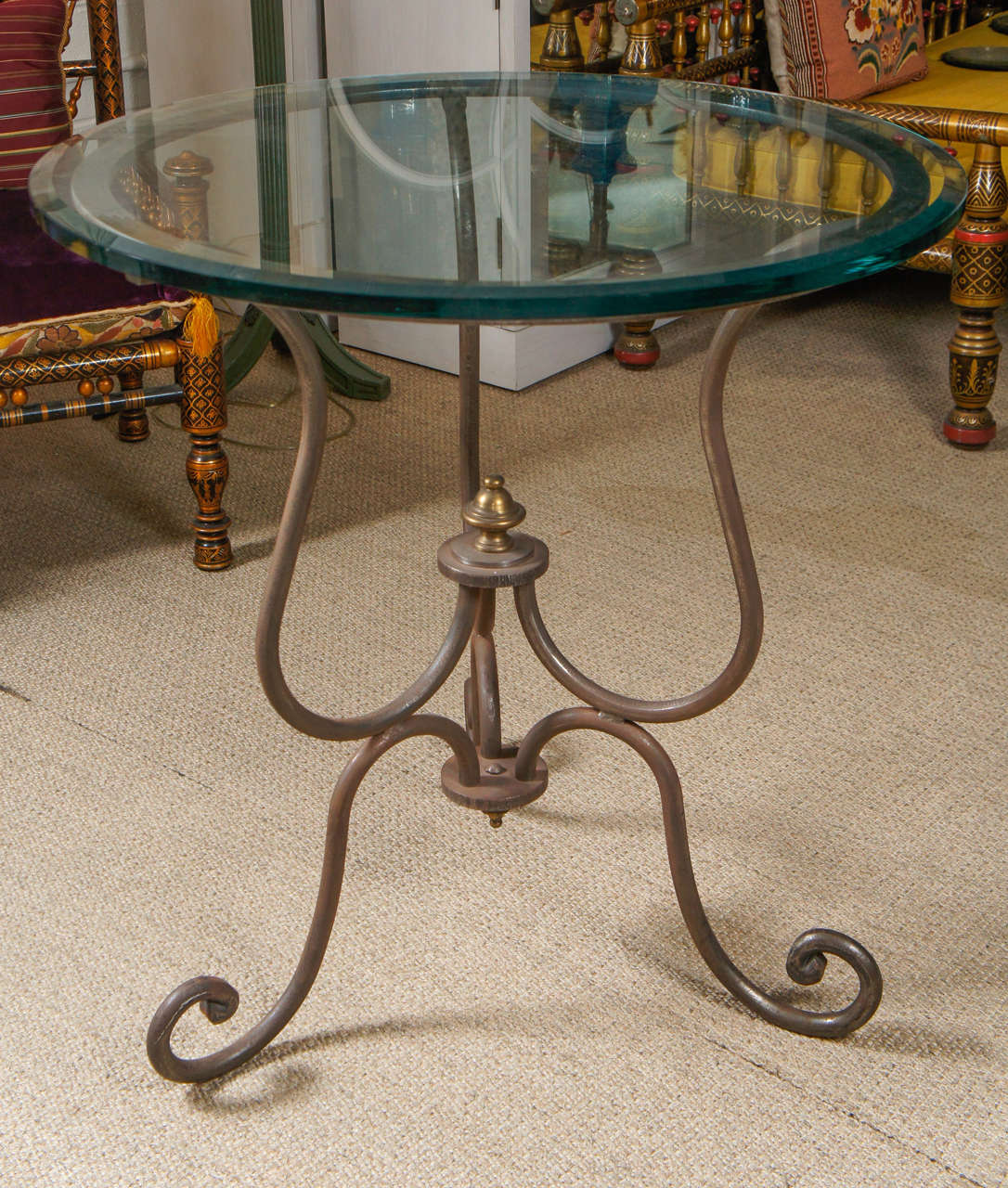Here is an iron table with a scroll motif and a thick glass top.