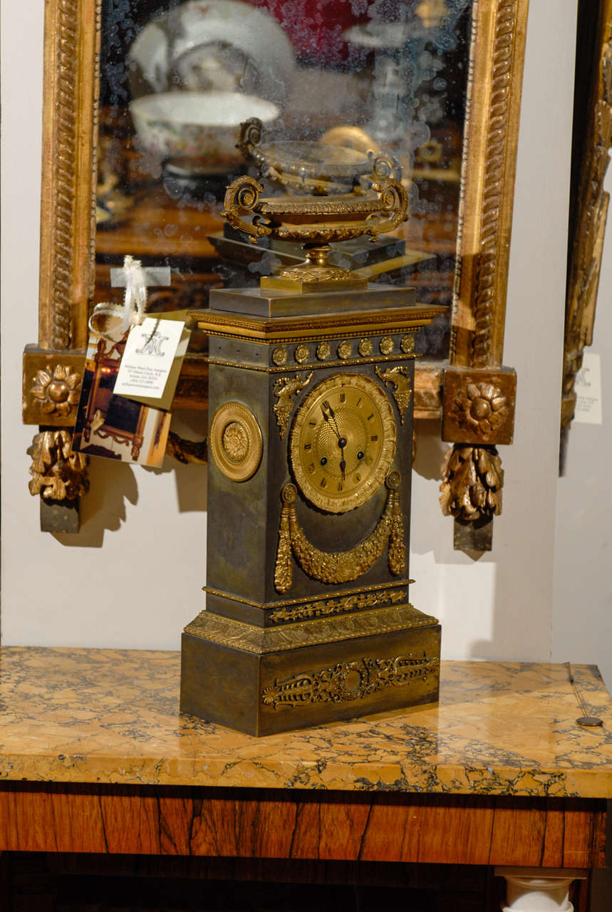 A large Neoclassical mantle clock in brass with ormalu mounts, urn and swag detail.   William Word Fine Antiques: Atlanta's source for antique interiors since 1956.