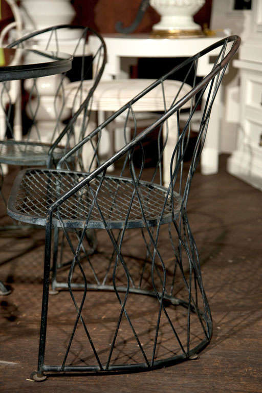 Wrought iron table and chairs attributed to Salterini. Unusual styled chairs with a glass top table.