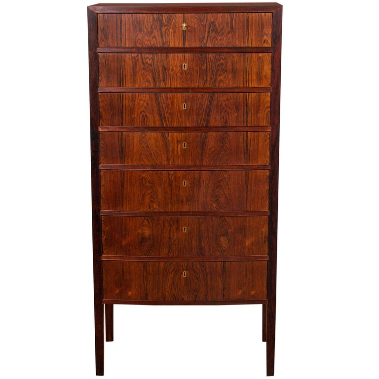 Ole Wanscher- 'Lingerie Chest' A Rosewood chest of drawers with slightly curved front and seven drawers with individual locks. Key included. Manufactured for retailer Illums Bolighus with paper label. Denmark, circa 1957.