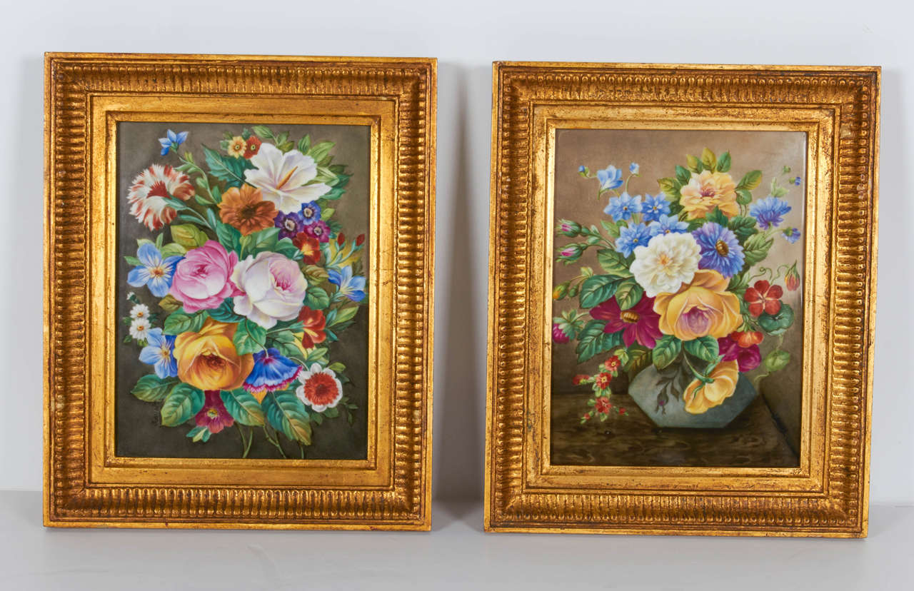 A fine pair of hand-painted porcelain plaques of floral still-life paintings with original giltwood frames. These beautiful floral still-life paintings have been hand-painted on porcelain plaques. The flowers are all very finely detailed and