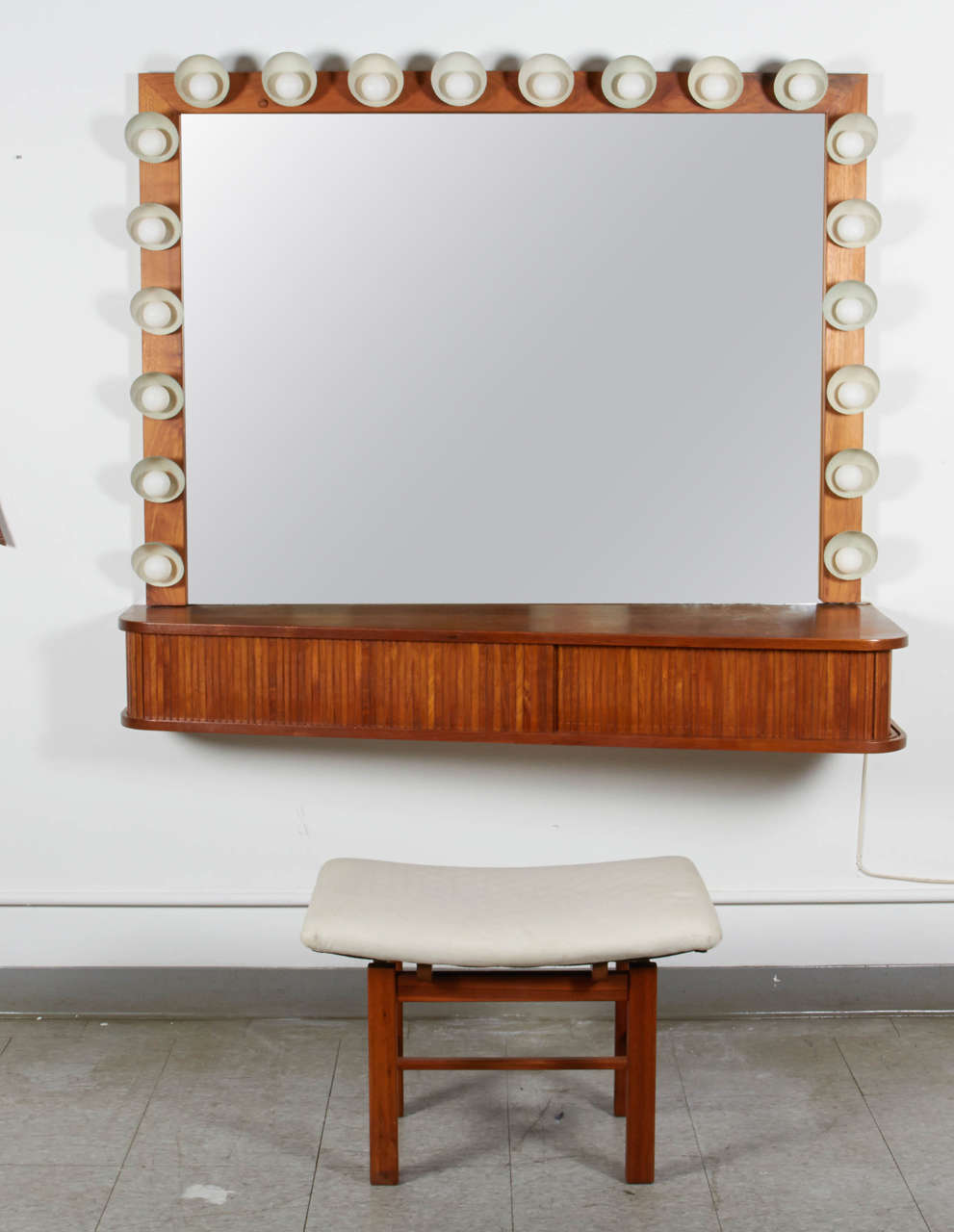 The custom-made vanity is rendered in clean and elegant design. The array of light covered by hemisphere shade in perforated metal gives ample illumination. The vanity comes with the matching stool. The seat measures D 17