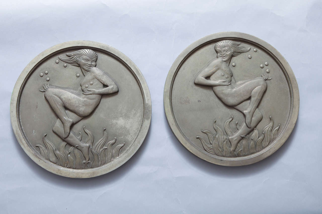 A pair of round American Art Deco silver plated bronze medallions each with a nude figure having stylized face above stylized waves.