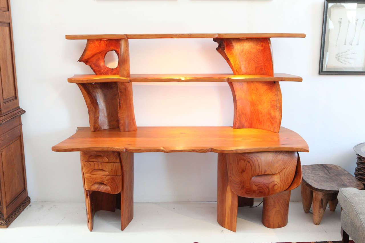 Commissioned sculptural desk from the 1970s in Red Cedar. Includes four drawers and six built in halogen lights on the shelves.