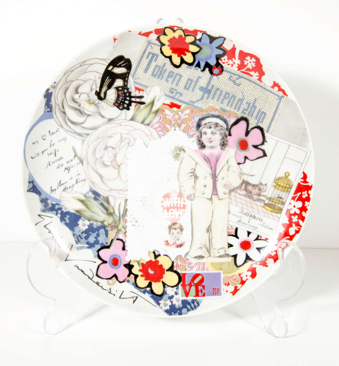 This pop art plate features a collage of multi dimensional Artwork and cations featuring the signature of Gloria Vanderbilt. Shown on a lucite stand and would add style and sophistication to any room.