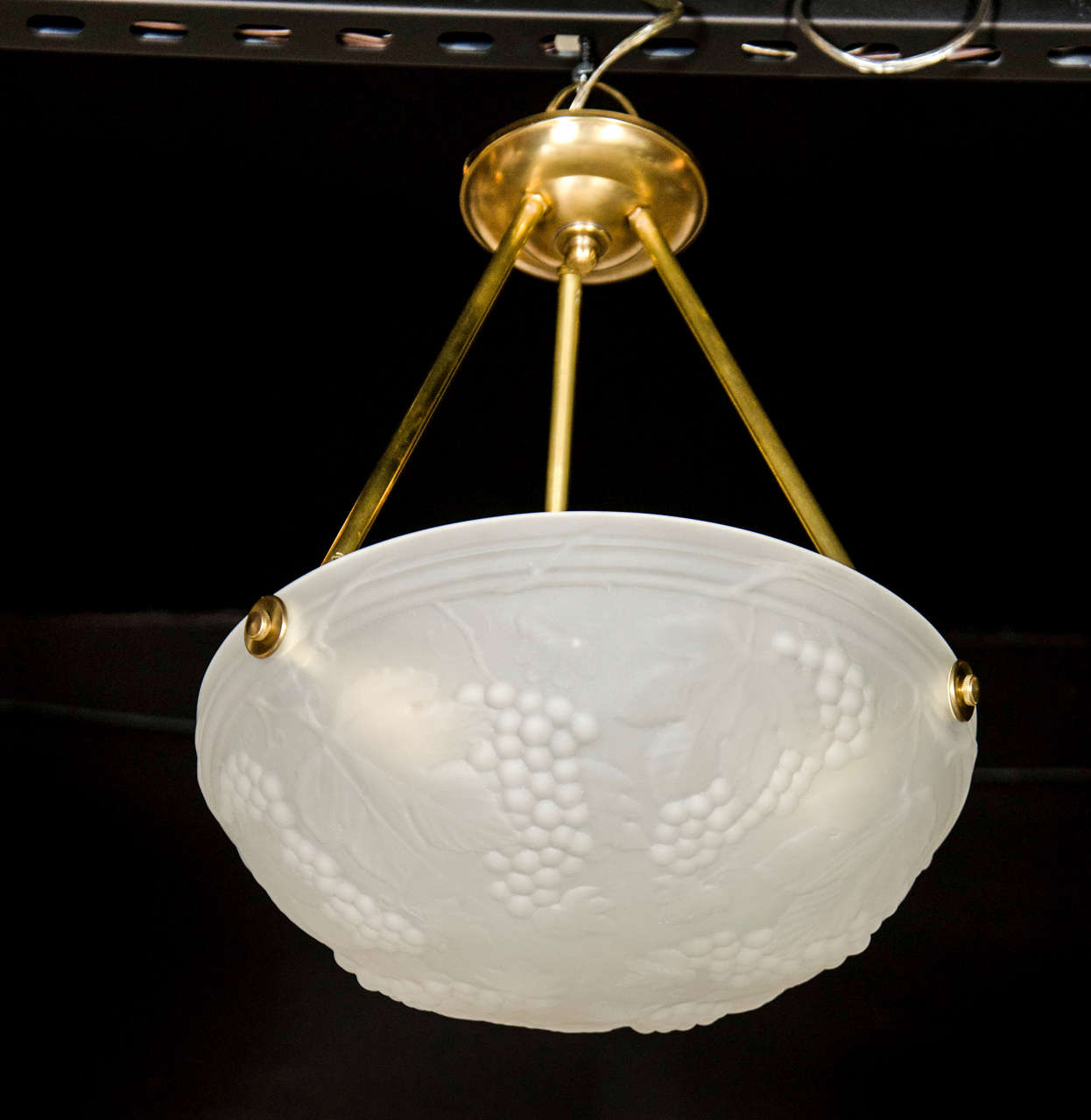 This elegant Art Deco flush mount chandelier features a frosted glass bowl shade with stylized grape and vine design with brass fittings. It is in excellent condition and has been newly rewired to American standards. The height can be adjusted to