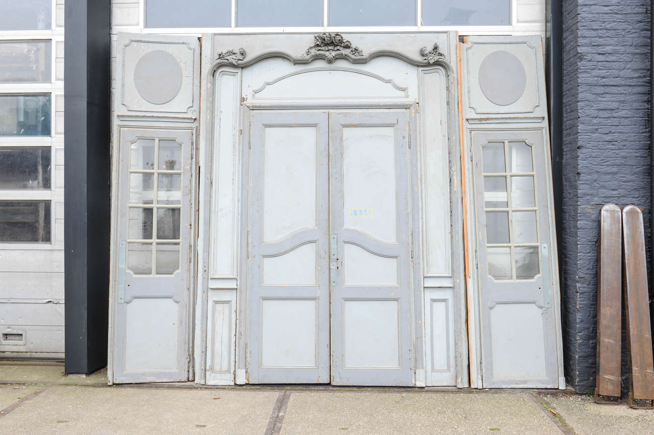 With original grey paint patina. 2 panels with glass (cupboard) doors within their original glass panes. 1 with a pair of double doors.  Measurements: Height 307 x width 2x73 cm + 229 cm. Door opening 235 x 136 cm.
