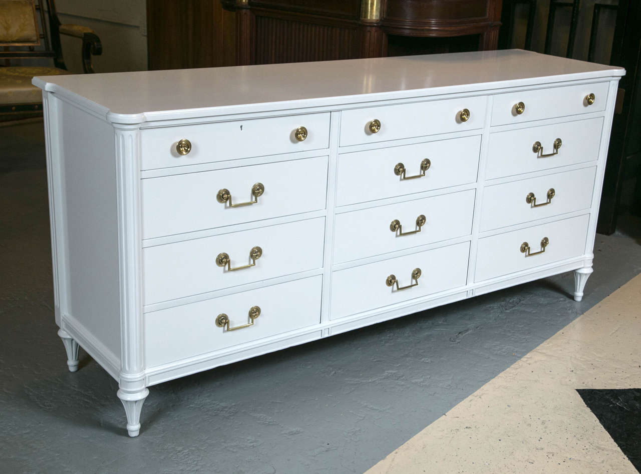 A Louis XVI style white lacquered triple dresser commode. This fine Hollywood Regency double commode is custom quality manufactured and has a wonderful white lacquered finish with Maison Jansen style mounts.