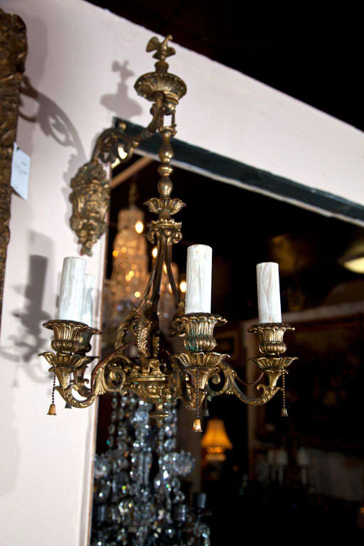 A PAIR OF 5 LIGHT  SCONCES IN THE FORM OF  CHANDELIERS. A SATYR MASK PLATE HOLDS  THE ARM FROM WHICH HANGS THE  5 LIGHT FIXTURE. BIRD FINIAL SURMOUNTS  IT ALL. CURNED ARMS WITH FOLIATE DECORATION.