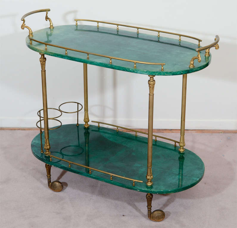 A vintage tea or bar cart with two shelves in emerald green lacquered goatskin and brass detailing. The piece is by Aldo Tura.  Reduced from: $3,750