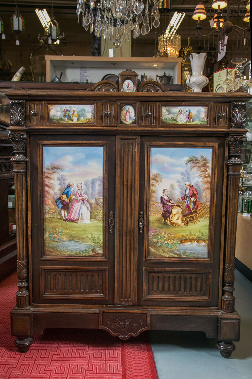 Antique cupboard or jelly cabinet with hand-painted pastoral medallion panels. This mahogany cabinet has a server design top with arch back and oval medallion. All of the porcelain panels are hand-painted with scenes which depict the time of Louis